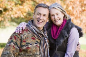 Happy couple in retirement taking an outdoors autumn fall walk