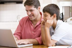 man helping young boy in kitchen with laptop smiling BYt cSs0rs scaled 1