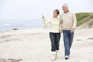 senior couple walking along beach Htphq0rs scaled 1